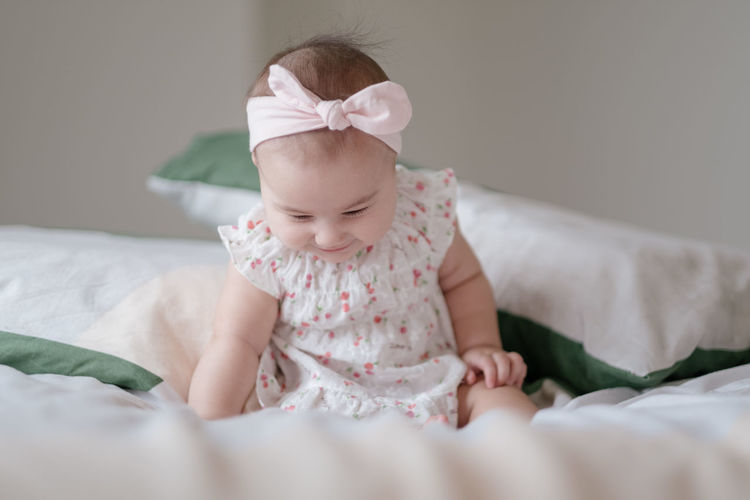 Cute baby girl lying on bed at home