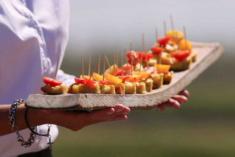 Midsection of woman holding food in serving tray