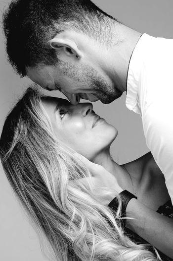 Close-up of smiling man embracing beautiful woman