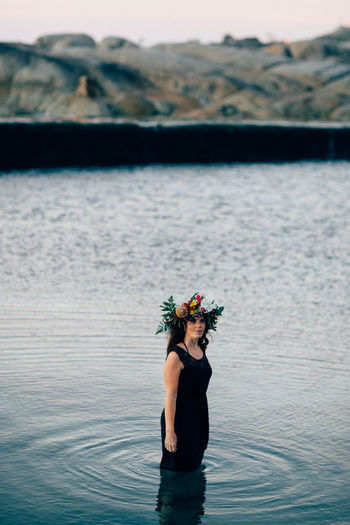 Woman wearing flowers in sea