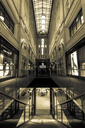 Shopping in Vienna Table Under The Surface View Urban Architecture Illuminated Built Structure Indoors  Building Lighting Equipment Direction Railing Absence The Way Forward No People City Ceiling Vienna Monochrome Symmetry Exceptional Photographs EyeEm Gallery Architectural Column Ceiling Light  Colonnade Passage Passageway Diminishing Perspective The Architect - 2019 EyeEm Awards