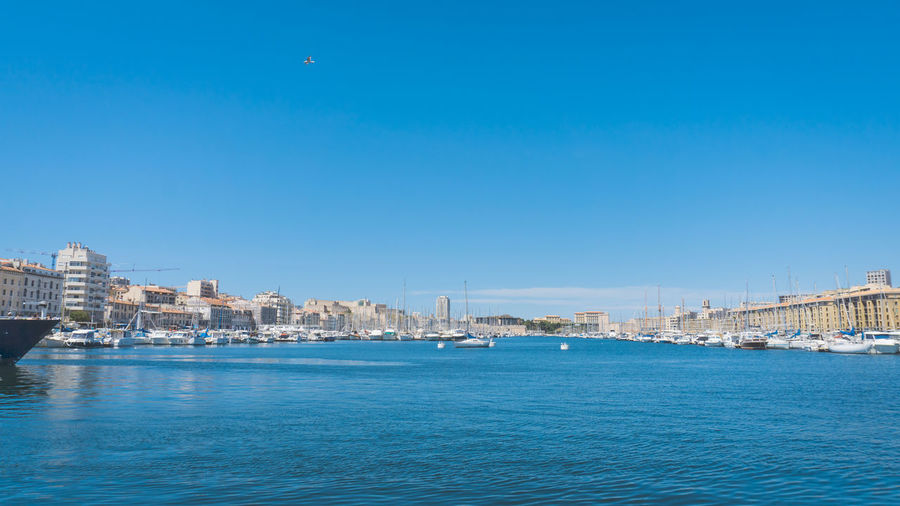 City by sea against clear blue sky