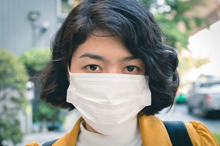 Portrait of beautiful young woman wearing mask standing outdoors