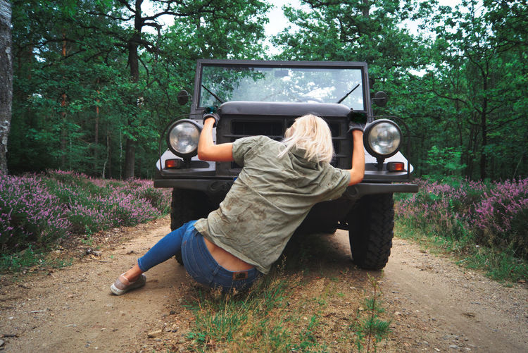 Woman sitting on road by breakdown jeep in forest