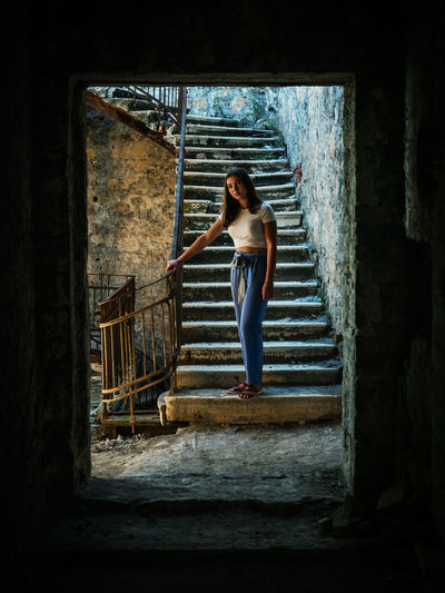Woman standing on staircase of old building