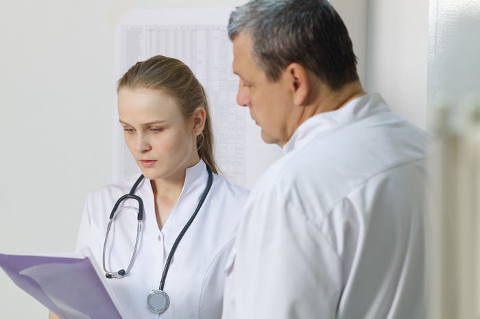 Active Analysis Assistant Caucasian Clinic Discuss Discussion Doctor  Health Hospital Hygienist Male Medical Men Nurse Office Profession Professional Sheet Sitting Specialist Women Young