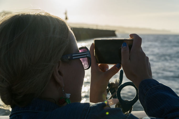 Close-up of woman photographing with mobile phone at beach