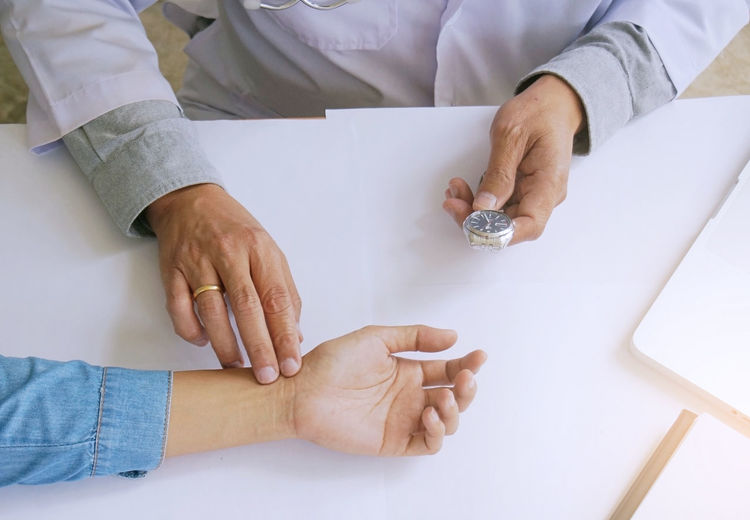 Midsection of doctor examining patient hand in hospital