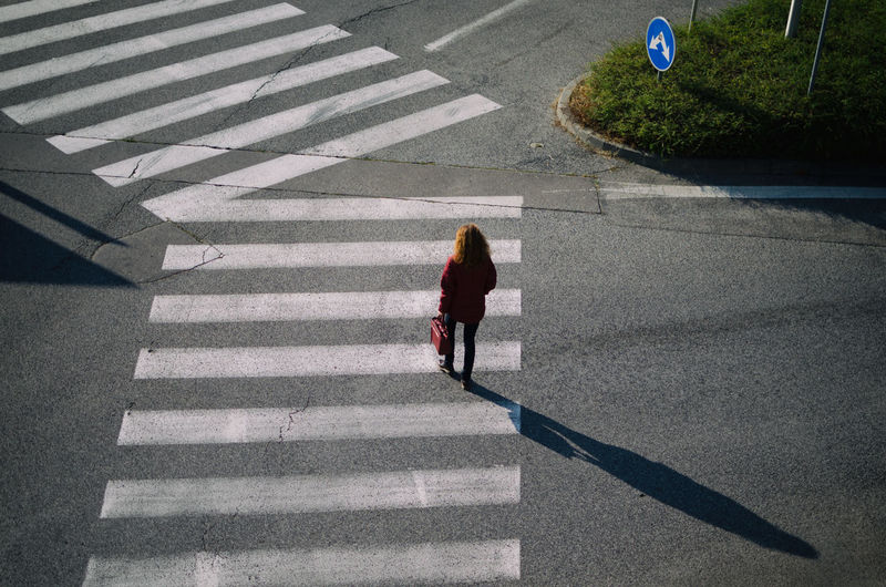 High angle view of woman walking on zebra crossing at street