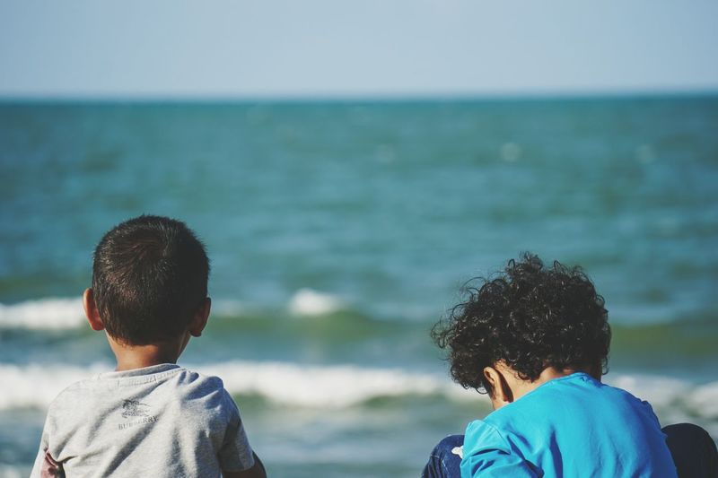 Cousins by the beach. Boy Girl Boy And Girl Beach Childhood Child Kids Water Young Women Sea Togetherness Men Women Friendship Bonding Rear View Clear Sky Shore Young Couple Children Sandy Beach Human Back This Is Family