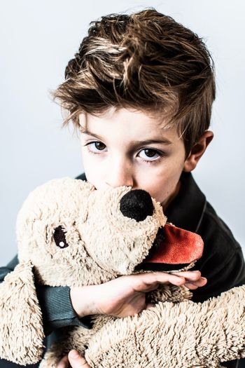 Portrait of boy with toy against gray background