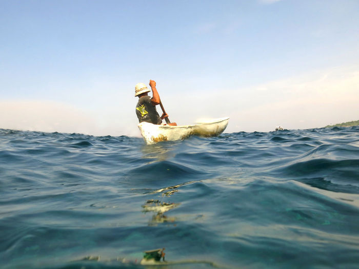 Rear View Of Man In Canoe On Sea Against Sky