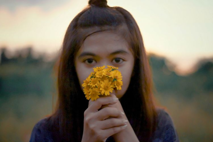 Close-up portrait of a girl holding flower