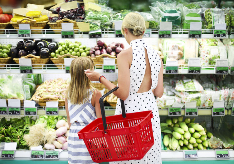 Mother holding strawberry in supermarket