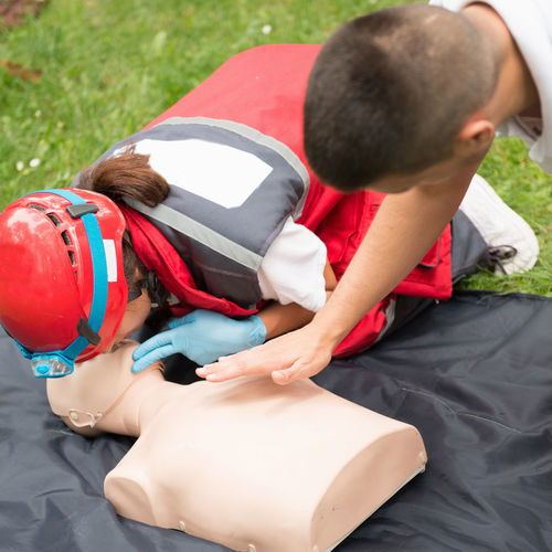 Healthcare workers practicing on cpr dummy at park