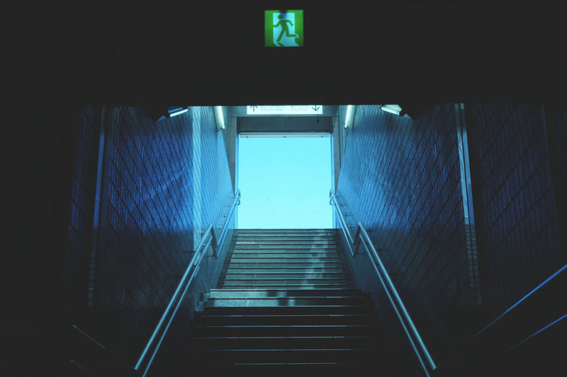 初めての投稿。 My first posted photo. Please evaluation for beginner Blue Dark Day Emergency Exit Exit Indoors  Japan Light At The End Of Tunnel Long Low Angle View No People Passage Railing Staircase Steps Steps And Staircases Subway Station Surrounding Wall The Way Forward Yokohama First Eyeem Photo