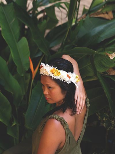 High angle view of thoughtful woman wearing flowers against plants