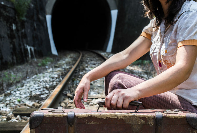 Side view of woman sitting on railroad track