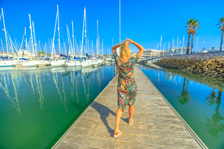 Summer holidays. Tourism in Algarve, Portugal. Lifestyle female tourist walking on wooden jetty at Marina de Lagos, Portugal, Europe. Caucasian woman enjoying at Bay of Lagos. Blue sky. Lagos Portugal Algarve Portugal Algarve Coastline Algarve Beach Algarve Cliffs And Beach Beach Sea Town Seascape Boat Portrait Pier Aerial View Cliff Jetty Boats Woman Females Girl Selfie Model Marina Bay Port One Person Water Full Length Real People Lifestyles Blue Sky Rear View Transportation Leisure Activity Nature Women Adult Nautical Vessel Day Young Adult Human Arm Standing Outdoors Arms Raised