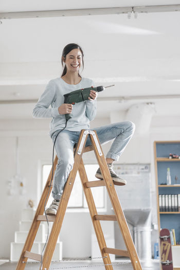 Full length of smiling young woman standing on ladder