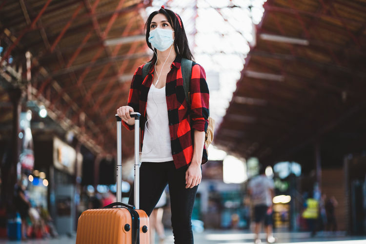 Low angel view of young woman wearing mask standing at airport