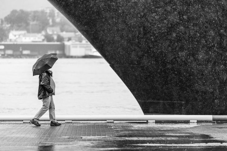 Man Walking With Umbrella On Wet Sidewalk By Cruise Ship During Monsoon
