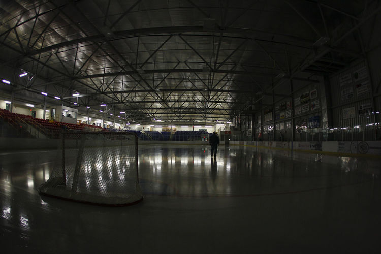 A lone arena worker walks across a fresh sheet of ice in a dark arena prior to the semi-final game at the 2015 Dudley Hewitt Cup. Ice Hockey Ojhlimages Fortfrances Ontario Hockey Brianwattsphotography First Eyeem Photo