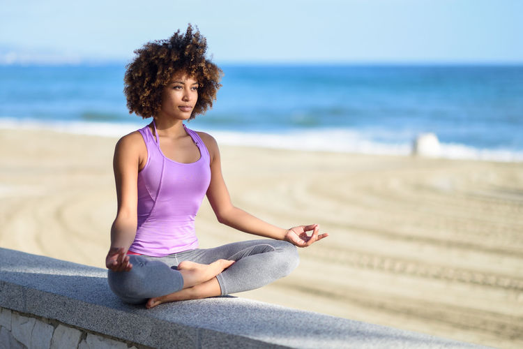 Black woman, afro hairstyle, doing yoga in the beach. Young Female wearing sport clothes in lotus figure with defocused background. One Person Curly Hair Relaxation Exercise Sport Exercising Yoga Full Length Sitting Leisure Activity Wellbeing Beach Land Lifestyles Cross-legged Young Adult Real People Healthy Lifestyle Relaxation Zen-like Hair Hairstyle Outdoors Tank Top Horizon Over Water Beautiful Woman