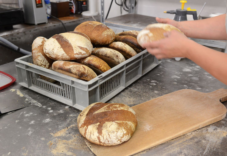 Close-up of hand holding bread at counter in kitchen