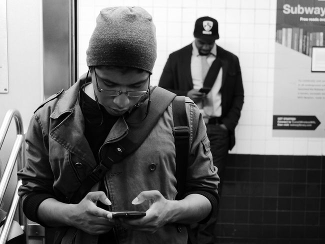NYC LIFE ♥ NYC Photography NYC Street NYC Street Photography NYC Subway Black And White Photography Day Devices Front View Holding Indoors  Knit Hat Lifestyles Looking Down Mobile Phone Real People Smart Phone Standing Technology Text Messaging Togetherness Two People Using Phone Wireless Technology Young Adult