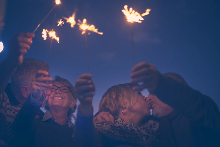 Low Angle View Of Senior Couple Playing With Sparklers Against Sky At Night