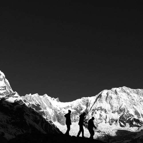 People walking by snowcapped mountains against clear sky