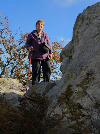 Low angle view of woman standing by rock formation against sky