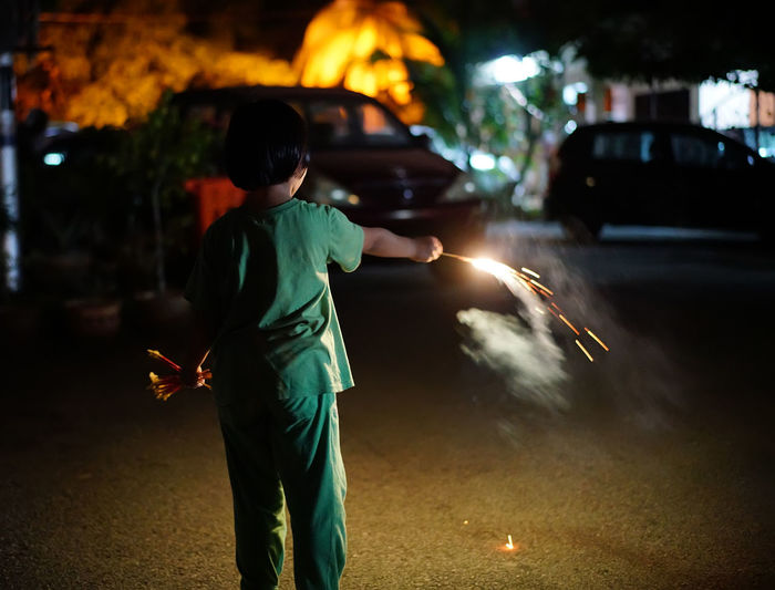 Boys Burning Car Casual Clothing Child Childhood City Firework Firework - Man Made Object Flame Focus On Foreground Glowing Illuminated Males  Men Motion Motor Vehicle Night One Person Outdoors Real People Sparkler Sparks Street Transportation