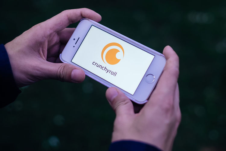 Closeup of hands holding iPhone screen with white CRUNCHYROLL APP LOGO Logo Body Part Close-up Communication Crunchyroll Finger Focus On Foreground Hand Heart Shape Holding Human Body Part Human Finger Human Hand Leisure Activity Lifestyles One Person Personal Perspective Real People Smartphone Streaming Text Tv Unrecognizable Person Western Script