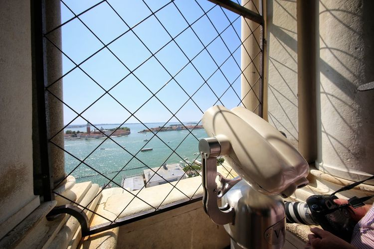 Telescope at observation point by window in city