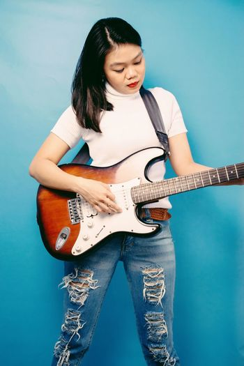 Young woman playing guitar against blue background