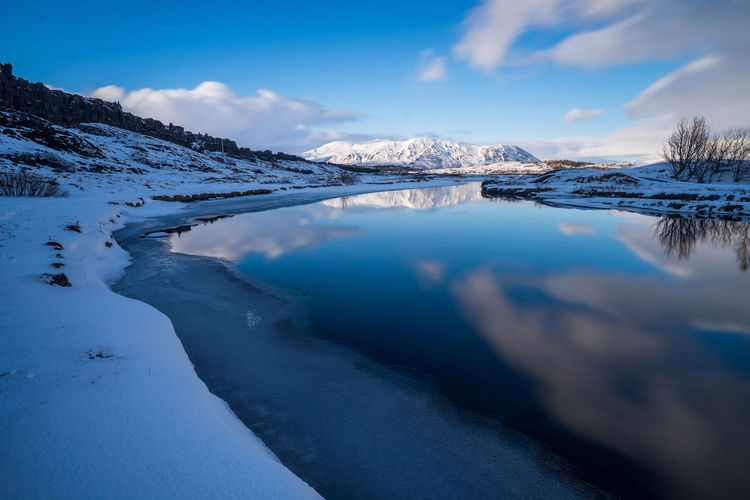 Frozen lake by mountain against sky during winter