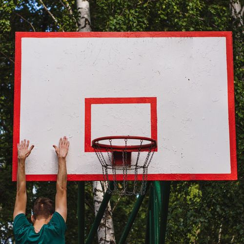 Low angle view of basketball hoop against red wall