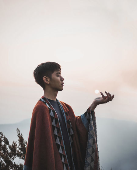 Young man looking away against sky