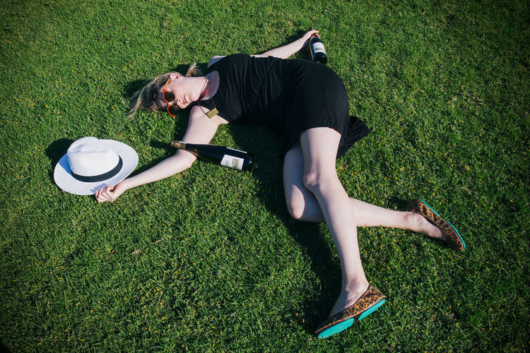 High Angle View Of Young Woman With Champagne Bottles Lying On Grassy Field