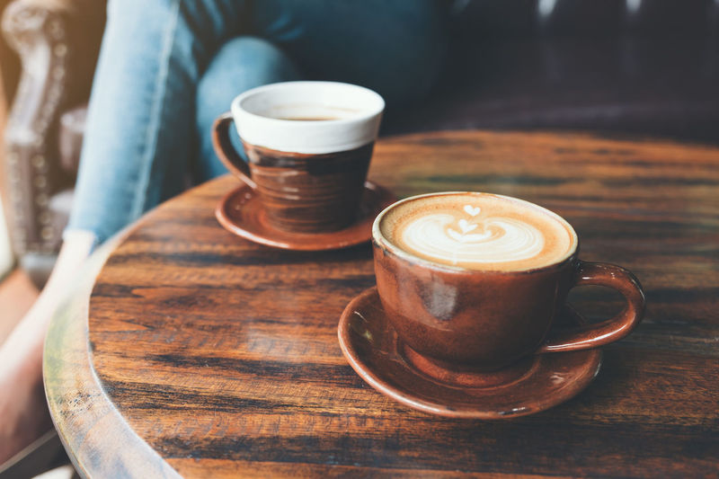 two cups of hot latte coffee on vintage wooden table with woman sitting in background Taste Table Style Space Shop Saucer Roasted Restaurant Refreshment Plate Old Mug Morning Mocha Milk Latte Hot Freshness Fresh Food Espresso Drink Delicious Dark Cup Coffee Closeup Close Cappuccino Caffeine Cafe Brown Breakfast Break Black Beverage Background Art Aroma Americano