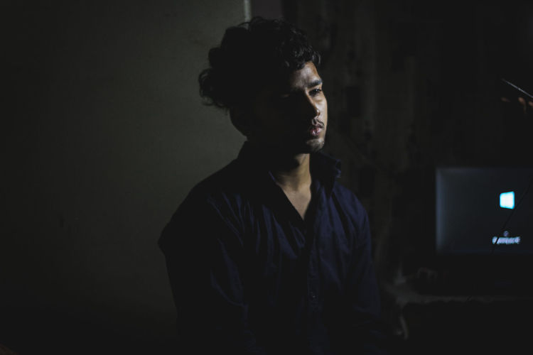 Portrait of young man looking away while standing in dark room