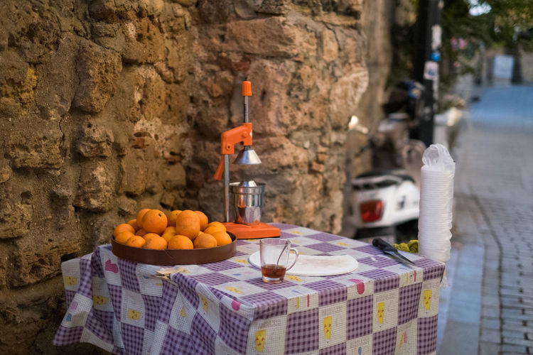 Oranges by juicer on table by footpath