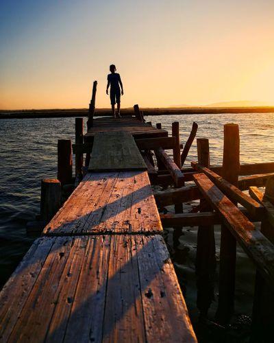 Silhouette boy walking on wooden pier in sea against sky