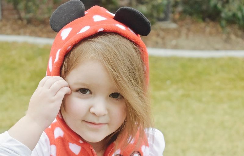 Adorable little 3 year old girl Children Headshots Kids Young Babygirl Child Childhood Close-up Cute Faces Girls Grass Background Growing Up Little Little Girl Outdoors Outside People Playing Playing Outside Portrait Pre School Days Toddlers  Toddleryears Wearing Mouse Ears Hoodie