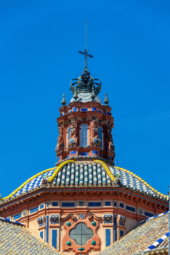 View of a colorful ornate dome with a beautiful blue sky in historic Seville, Spain Sevilla Seville SPAIN Europe European  Semana Santa Holy Week Easter Travel Destinations Travel Tourism Springtime Spring Architecture Sky No People Built Structure Building Exterior Day Medieval Medieval Architecture City Center Historic Center Downtown Religion Christianity Christian Catholic Catholicism Belief Building Spirituality Place Of Worship City Church Cathedral Blue Clear Sky Dome Ornate
