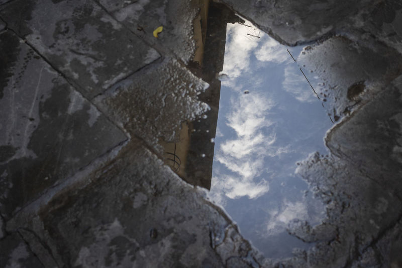 Low angle view of buildings reflecting in puddle