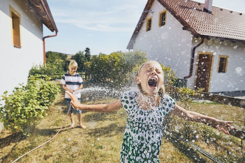 Boy Spraying Water On Sister Standing In Yard