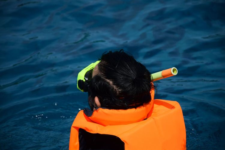 Rear view of man wearing life jacket and scuba mask while swimming in sea